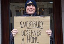 Steve Logan in his 14 Hours Homeless beany holding a sign that says 'Everybody Deserves a Home