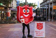 Red shield mascot with collecting bucket