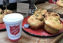 A cup with 'The Salvation Army' wording on it amongst cafe food items