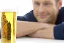 Man looks at a full glass of beer