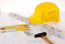 a builders hard hat next to blueprints of a building