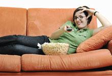 a woman lying on the couch watching movies