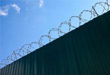 a wall with barbed wire on top