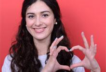 A girl making a heart symbol with her hands