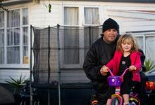 A man with daughter outside a housing