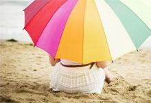 a woman under an umbrella on the beach