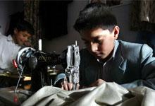 Two boys (aged 10 and 13 ) sew clothing at the Sajaad Tailor shop in Kabul, Afghanistan.