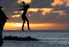 a girl jumping into the sea