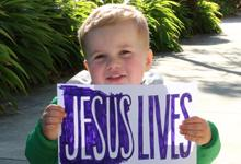 Cute little boy holds a sign saying 'Jesus Lives'