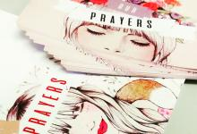 Two sets of cards with 'Our Prayers' written on them on top of a woman's head