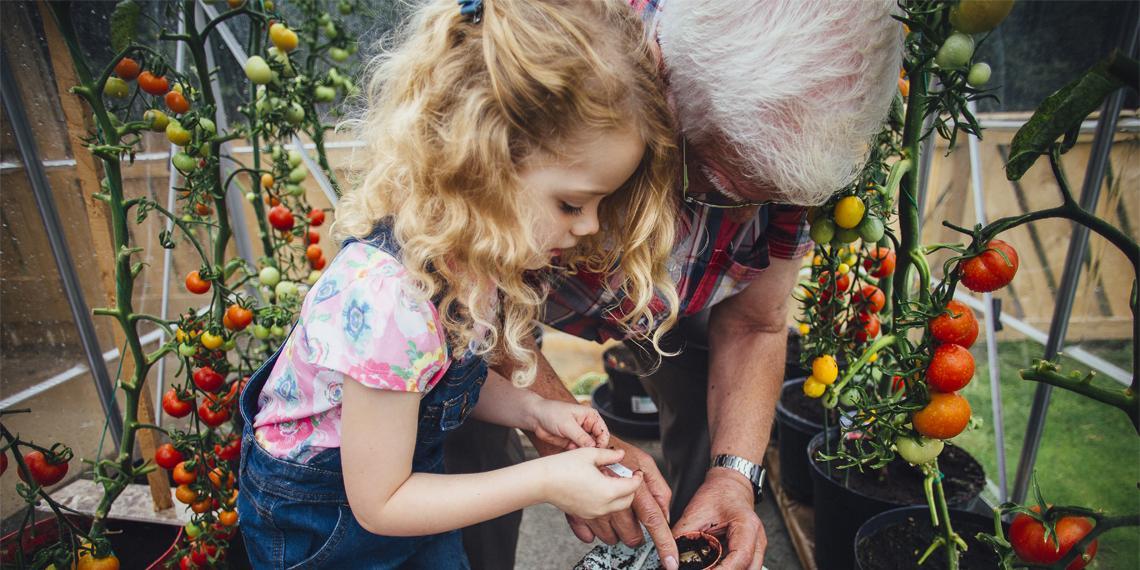 a child and grandparent tending a garden