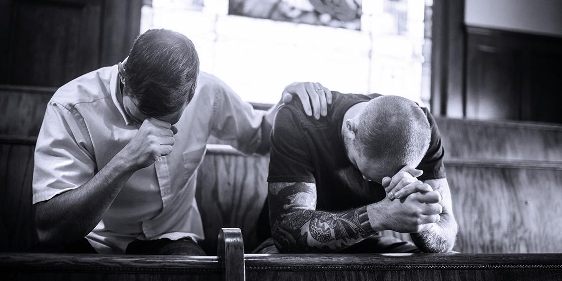 two men praying together in church
