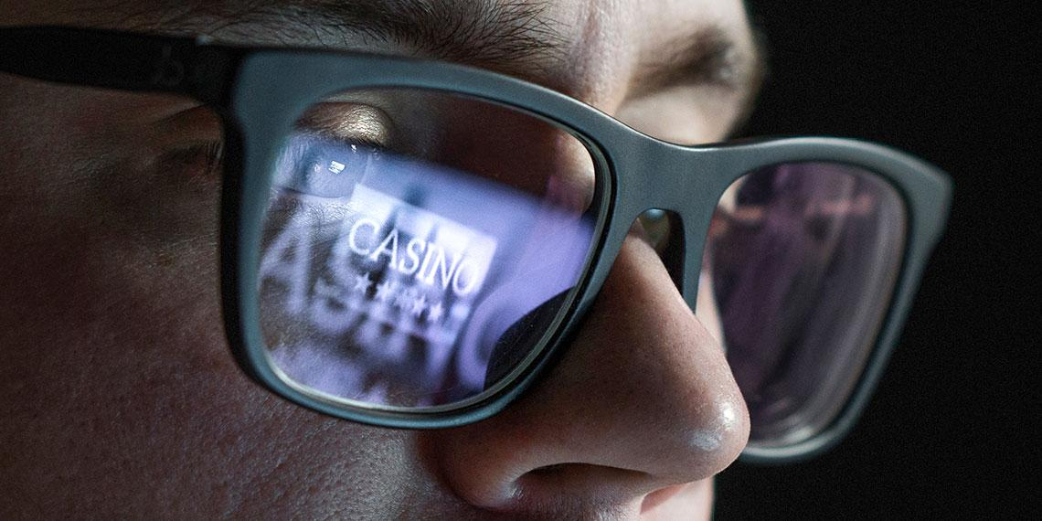 Close up of face with computer screen reflection in glasses showing they are at an online casino