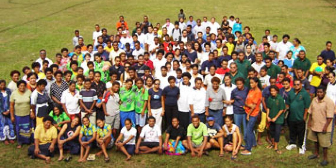 Large group of people standing on a sports field