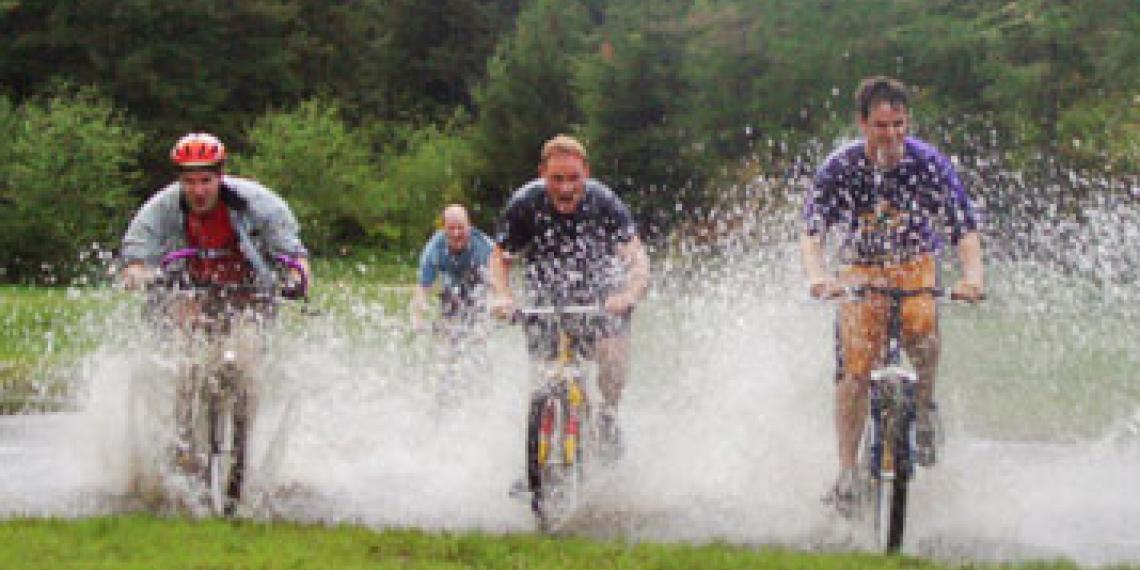 Men biking through a puddle