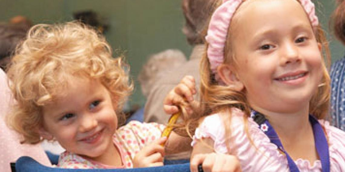 Two sisters playing with each other's hair during a church service