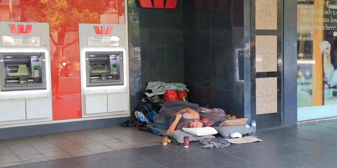 a homeless couple sleeping in front of a Westpac bank branch