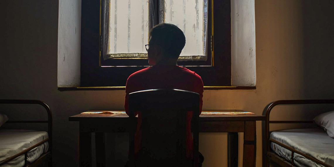 Person by window in sparse room