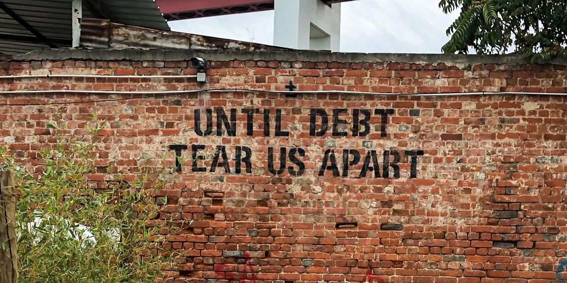 "graffiti on wall ""until debt tear us apart"""
