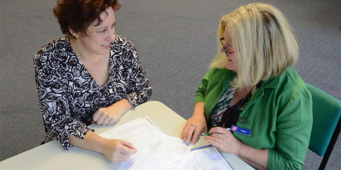 two women talking over paperwork