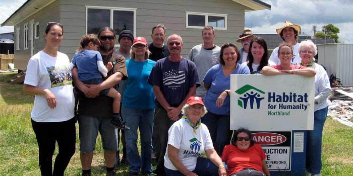 People grouped around a habitat for humanity house