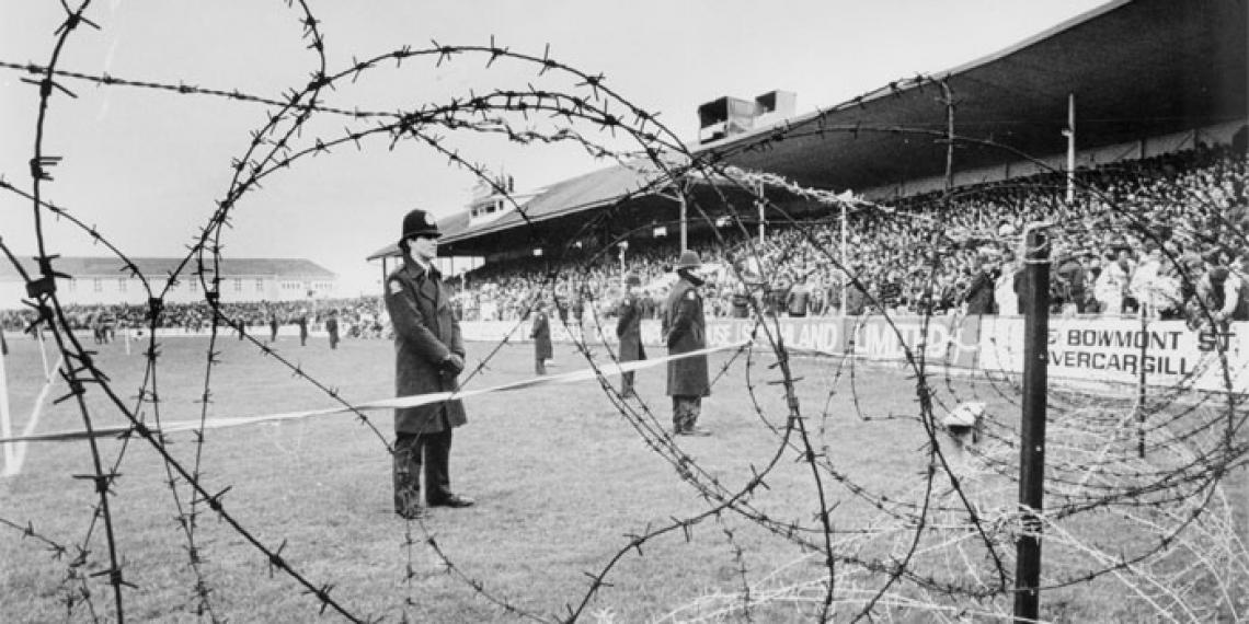 Police stand watch during the Springboks vs. Southland game at Invercargill's Rugby Park on 8 August 1981 (Photographer: Stuart Menzies / Ref: EP-Ethics-Demonstrations-1981 Springbok Tour-01 / Alexander Turnbull Library, Wellington, New Zealand)