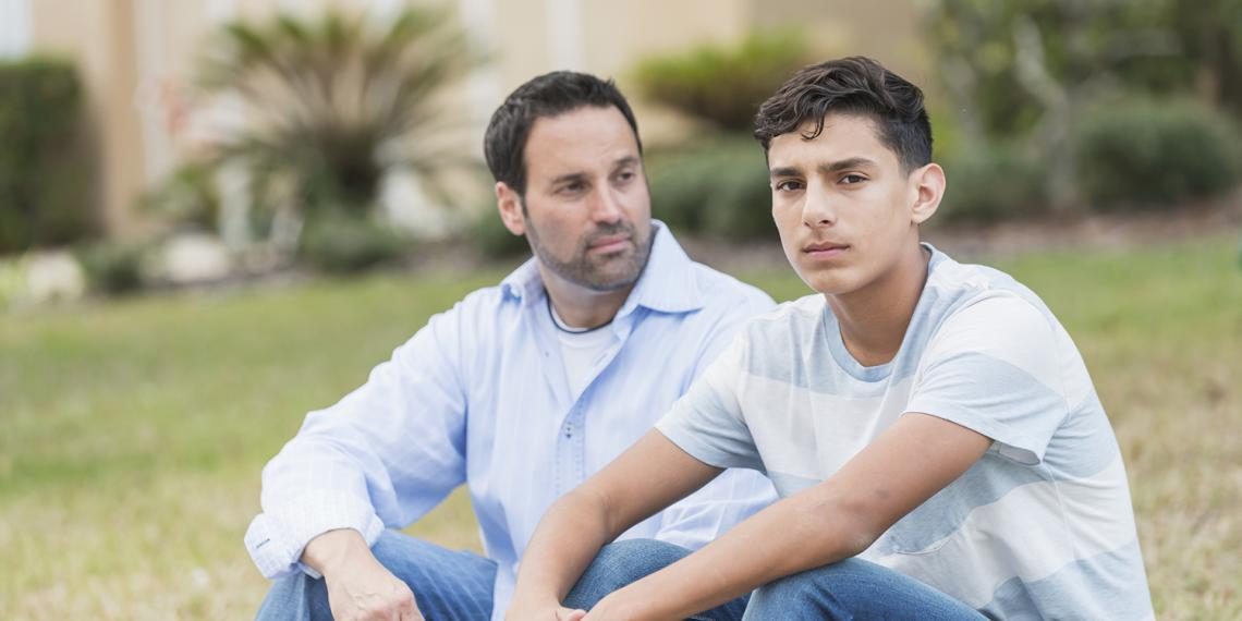 a man talking with his teenage son