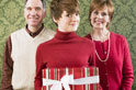 Woman holiding a present in front of parents