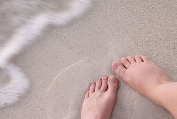 Feet next to waves