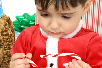 Child frowing at a broken candy cane