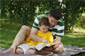 father reading bible with son